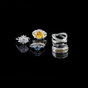 53456835 - collection of rings with colorful gems on black background